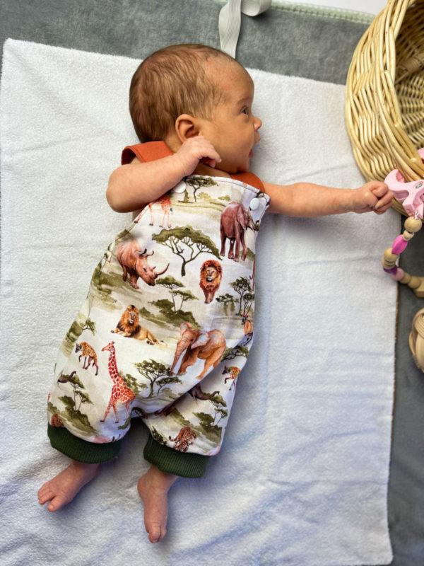 bebé con el peto de tela estampada safari comfeccionado a mano